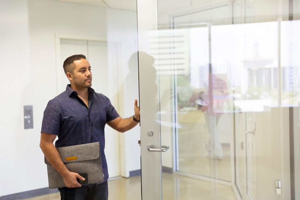 A man standing beside the office glass door