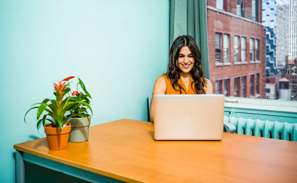 a smiling woman in front of an open laptop
